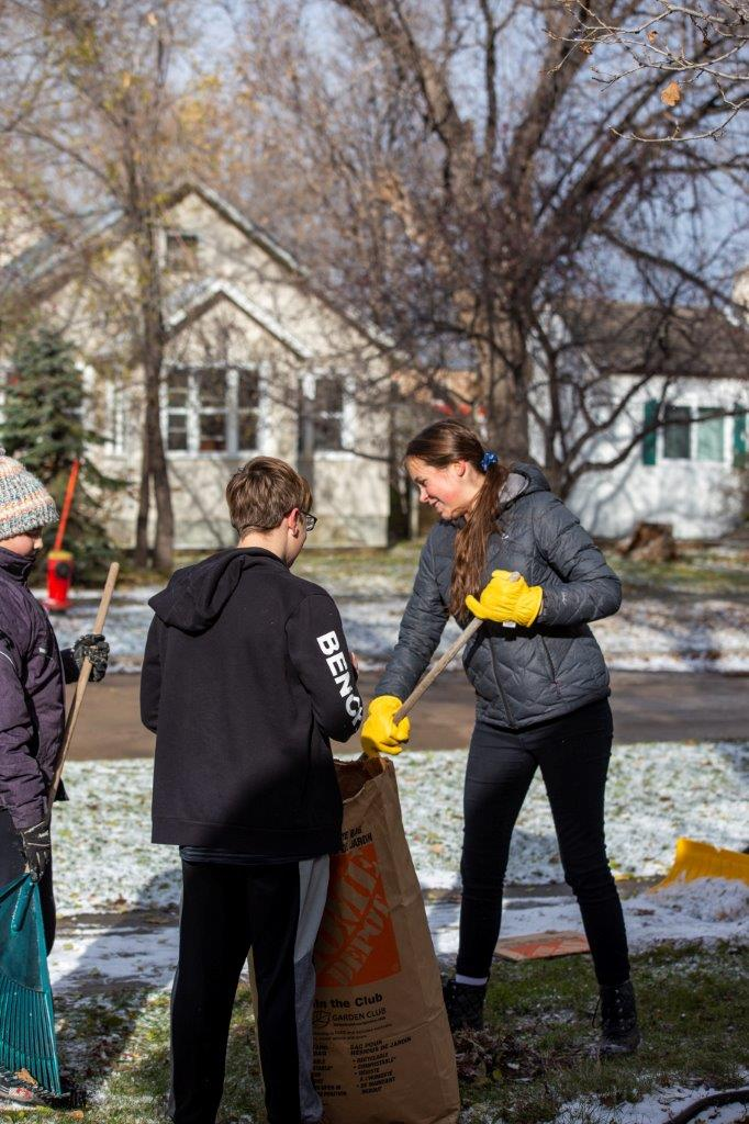 Students and teachers cleaning the leaves after the fall in the school area